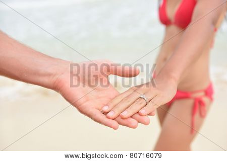 Newlyweds casual beach wedding or proposal concept - closeup of couple holding hands and marriage rings. Young loves in love.