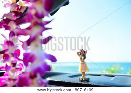 Hawaii travel car - Hula girl dancing on dashboard and lei during road trip.