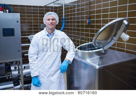 Smiling biologist leaning against storage tank in the factory