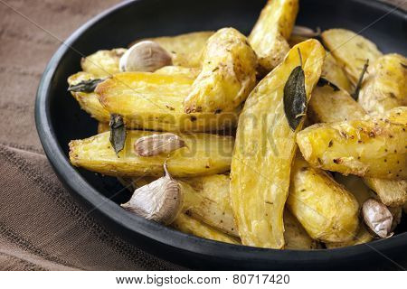 Roasted fingerling or kipfler potatoes, with sage leaves, in black dish.