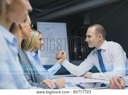 business, rivalry and people concept - businesswoman and businessman arm wrestling during meeting in office