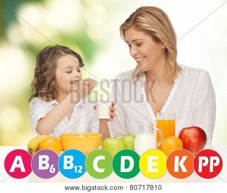 people, healthy lifestyle, family and food concept - happy mother and daughter eating healthy breakfast over green background with vitamins