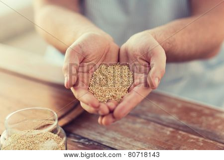 cooking and home concept - cloes up of male cupped hands with quinoa