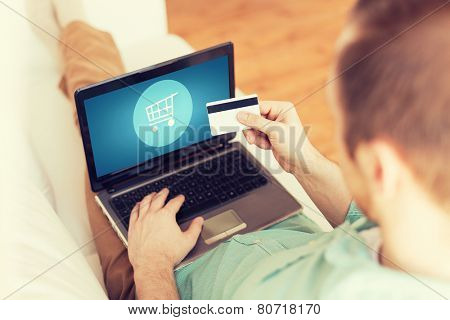 technology, shopping, banking, home and lifestyle concept - close up of man with laptop computer and credit card at home