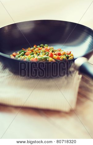 cooking, food and home concept - close up of wok pan with vegetables