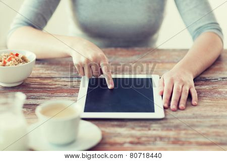 health, technology, internet, food and home concept - close up of woman pointing finger to tablet pc computer screen