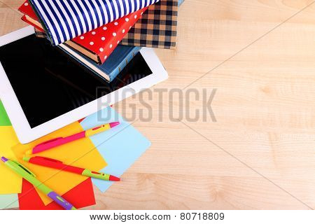 Pile of books with tablet on wooden table background