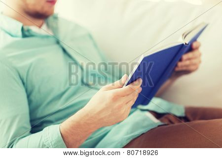 leisure, education, literature and home concept - close up of man and sitting or lying on couch and reading book at home