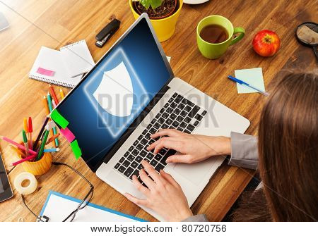 Woman working with laptop placed on wooden desk with digital scheme of security. Shot from aerial view