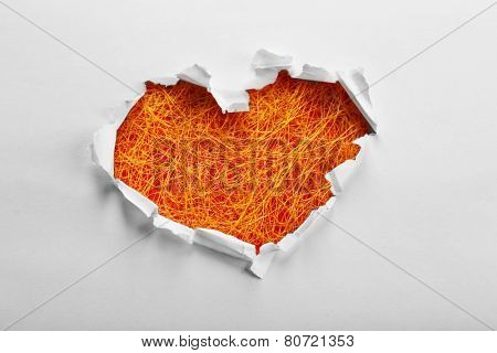 White torn paper heart over textured background