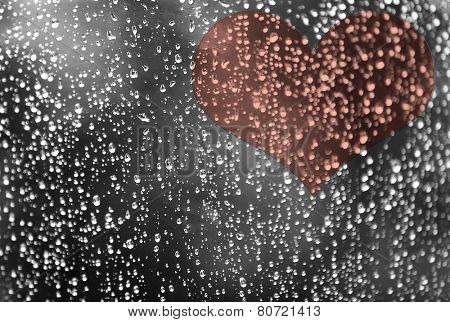 Rain water drops on window glass with heart
