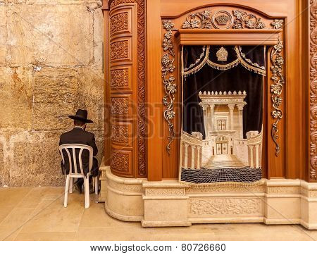JERUSALEM, ISRAEL - JULY 10, 2014: Prayer sits near Carving wooden cabinet with Torah scrolls in Cave Synagogue - a part of famous Western Wall (aka Wailing Wall), sacred place in Judaism.