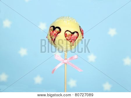 Tasty cake pop on blue background