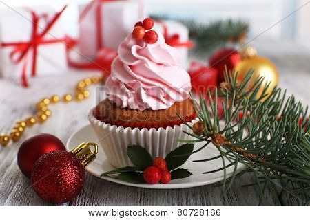 Cup-cake with cream on saucer with Christmas decoration on wooden table background