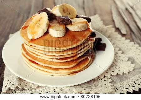 Stack of delicious pancakes with chocolate, honey and slices of banana on plate and napkin on wooden table background