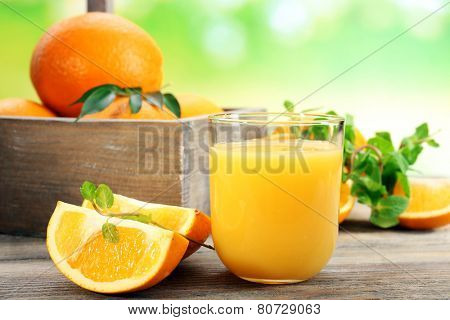 Glass of orange juice with crate of oranges and slices on wooden table and bright background