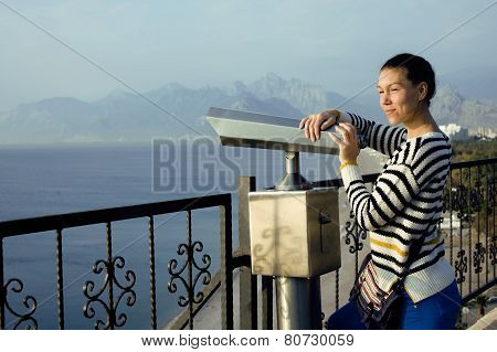 young real woman looking through telescope at sea viewpoint in A