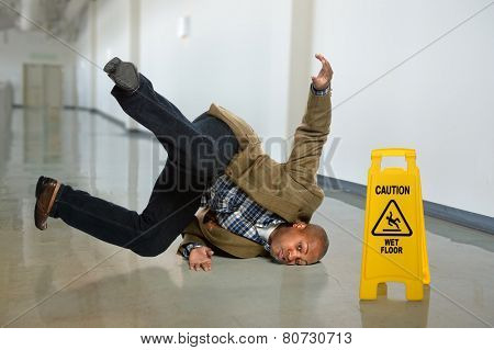 African American businessman falling on wet floor in office