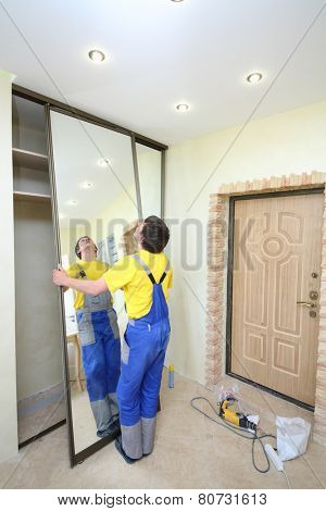 Worker puts mirror doors in closet in hallway