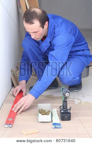 Master puts floorboards along the line near wall