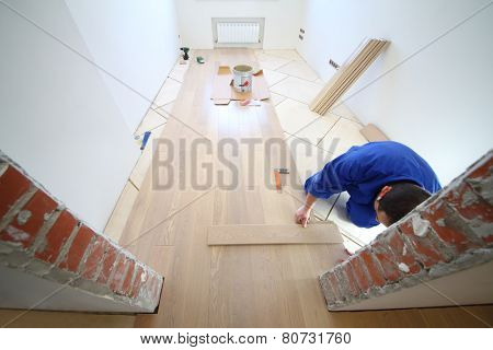 Worker  in white room where the laminate is laid, view through doorway