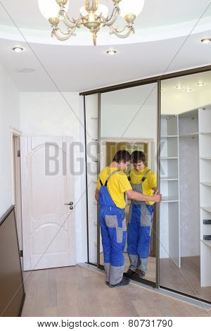 Young man fixing mirrored door on corner closet in room
