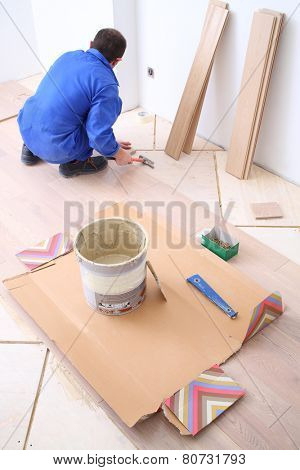 Man puts laminate flooring in white room