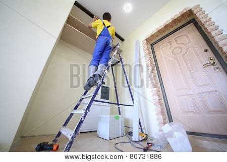 Man standing on ladder fixes shelves to wall for closet in hallway, bottom view