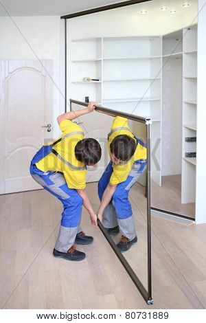 Young worker raises mirrored door on corner closet in room