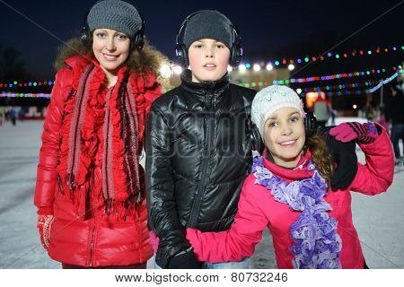 Happy mother with son and daughter on silent disco skating in winter evening