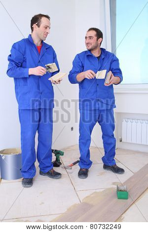 Two builders apply glue to the board for floor with a spatula in white room