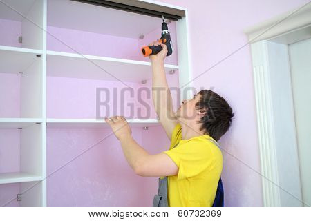 Man installing guide rails for sliding wardrobe in room with pink walls
