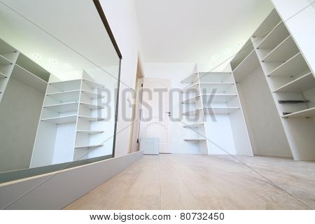 Installation of white corner sliding wardrobe and its reflection in mirror