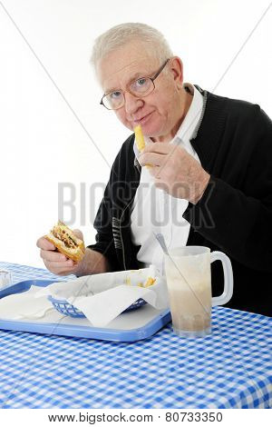 A senior adult man enjoying a meal of burger, fries and a root beer float.  On a white background.