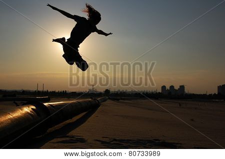 Man jumps over the pipe in backlight on the dawn of the day