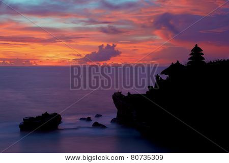 Silhouette of Pura Tanah Lot at coloured sunset.