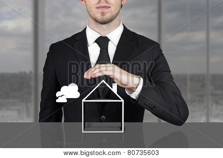 Businessman Holding Protective Hand Above Empty Building Symbol