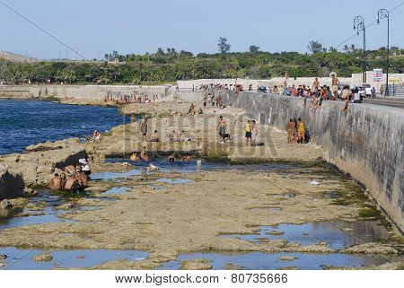 People sunbathe at the Malecon seawall in Havana, Cuba.