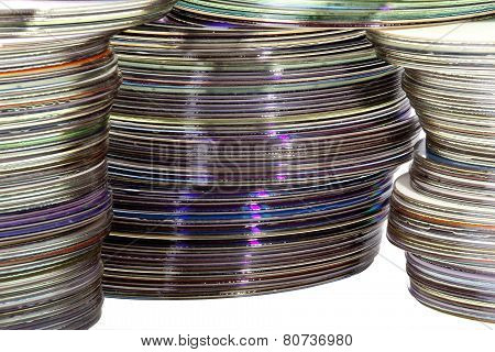 Three Piles Of Colored Shiny Compact Discs
