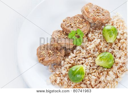 Medallions and brown rice with brussels sprouts on white wood background