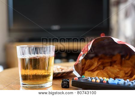 Unhealthy Food On Table With Skull Dice And Tv In Background