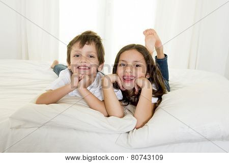 7 Years Old Little Girl Posing On Bed Or Couch Together With Her 4 Years Old Small Brother Smiling H