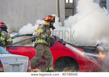 Firemen training on a burning car at the New Baltimore Fire Station in New Baltimore, Virginia.