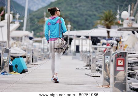 relaxed young woman walking in marina with yacht boats in background