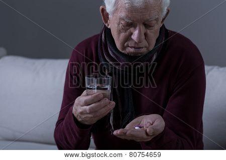 Ill Senior Man Taking Medicament