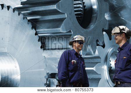 engineers, mechanics with large cogs and gears machinery