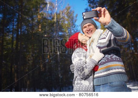 Amorous girl kissing her boyfriend while he making their selfie in natural environment