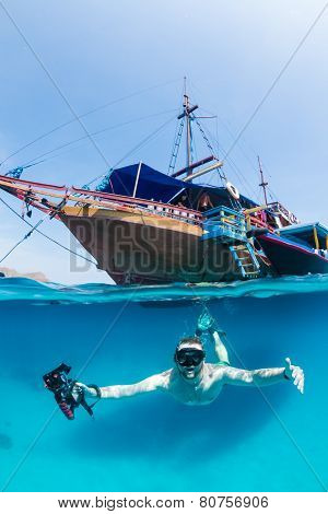 Snorkeller under a traditional wooden boat in tropical waters