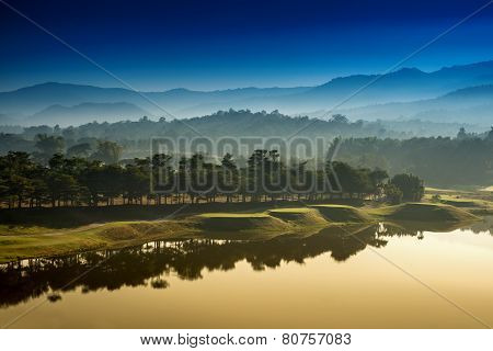 Golf Course At Dawn Backlit By Rising Sun