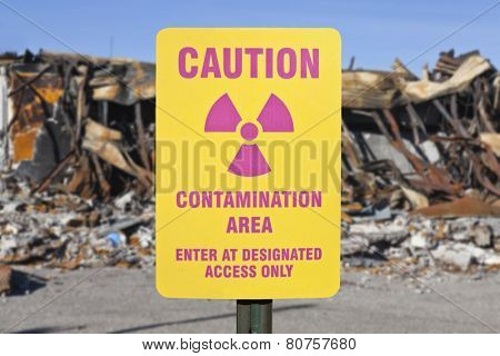 Contamination area warning sign with ruin background.